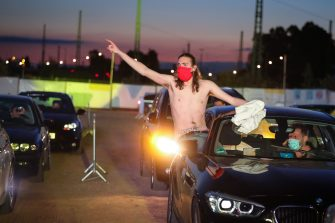 """BONN, GERMANY - MAY 15: Supporters reacts from their cars as German singer Heino performs on stage during the first BonnLive drive-in concert at Am Westwerk during the Coronavirus crisis on May 15, 2020 in Bonn, Germany. The project """"BonnLive Autokonzerte"""" is a series of drive-in concerts with musicians of different genres. The area provides space for about 200 cars. Drive-ins are becoming an increasingly popular venue for singers, theater groups, and even churches to hold events while adhering to Coronavirus lockdown measures. Two peoples are allowed to attend per vehicle and the attendees must remain in their cars. (Photo by Andreas Rentz/Getty Images)"""