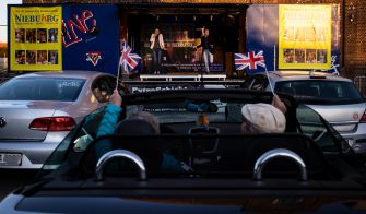OBERHAUSEN, GERMANY - APRIL 21: The Theater an der Niebuhrg theatre group performs musical hits at a makeshift stage on a truck for a drive-in audience during the coronavirus crisis on April 21, 2020 in Oberhausen, Germany. The drive-in theatre is a means for the group to continue performing and selling tickets while their regular venue remains closed as part of measures aimed at slowing the spread of the novel coronavirus. Across Germany theatres, museums, cinemas, symphonies, opera halls, ballets and other cultural institutions are struggling to make it through the coronavirus lockdown. (Photo by Lars Baron/Getty Images)