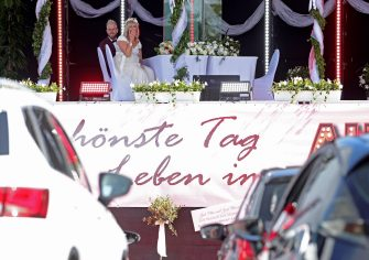 epa08402439 The bridal couple Janine and Philip Scholz during the wedding ceremony at a drive-in cinema in Duesseldorf, Germany, 05 May 2020. On the parking lot of the exhibition area the first weddings are held in a drive-in cinema in Germany. Due to the ongoing pandemic of COVID-19 disease caused by the coronavirus SARS-CoV-2, weddings in Germany are only possible in the registry office without an audience.  EPA/FRIEDEMANN VOGEL