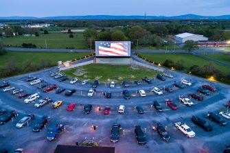 epa08398179 A photo taken with a drone shows movie-goers listening to The Star Spangled Banner before the start of the movie Trolls World Tour at the newly re-opened Family Drive-in Theatre in Stephens City, Virginia, USA, 02 May 2020. Theatre owner James Kopp successfully lobbied Virginia governor Ralph Northam to reopen his drive-in during the coronavirus pandemic, by promising to adhere to strict social distancing guidelines.  EPA/JIM LO SCALZO