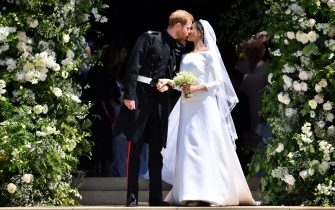 TOPSHOT - Britain's Prince Harry, Duke of Sussex kisses his wife Meghan, Duchess of Sussex as they leave from the West Door of St George's Chapel, Windsor Castle, in Windsor, on May 19, 2018 after their wedding ceremony. (Photo by Ben STANSALL / POOL / AFP)        (Photo credit should read BEN STANSALL/AFP via Getty Images)