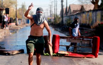 A demonstrator gestures during clashes with riot police within a protest against Chilean President Sebastian Pinera's government amid the COVID-19 pandemic, in Santiago, on May 18, 2020. - Villagers in the populous commune of El Bosque, in southern Santiago, clashed with the police after protesting the lack of food and work as a result of the crisis caused by the coronavirus, which keeps the Chilean capital in total quarantine. (Photo by RAMON MONROY / AFP) (Photo by RAMON MONROY/AFP via Getty Images)