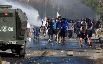 Demonstrators clash with riot police during a protest against Chilean President Sebastian Pinera's government amid the COVID-19 pandemic, in Santiago, on May 18, 2020. - Villagers in the populous commune of El Bosque, in southern Santiago, clashed with the police after protesting the lack of food and work as a result of the crisis caused by the coronavirus, which keeps the Chilean capital in total quarantine. (Photo by Pablo Rojas / AFP) (Photo by PABLO ROJAS/AFP via Getty Images)