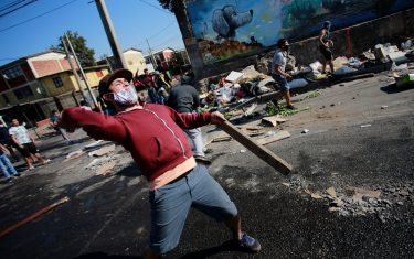 TOPSHOT - Demonstrators clash with riot police during a protest against Chilean President Sebastian Pinera's government amid the COVID-19 pandemic, in Santiago, on May 18, 2020. - Villagers in the populous commune of El Bosque, in southern Santiago, clashed with the police after protesting the lack of food and work as a result of the crisis caused by the coronavirus, which keeps the Chilean capital in total quarantine. (Photo by Pablo Rojas / AFP) (Photo by PABLO ROJAS/AFP via Getty Images)