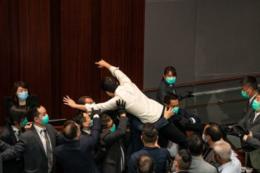 HONG KONG, CHINA - MAY 18:  Pro democracy lawmaker Ted Hui is removed by security during a scuffle with pro Beijing lawmakers at the House Committee's election of chairpersons, presided by pro-Beijing lawmaker Chan Kin Por  at the Legislative Council on May 18, 2020 in Hong Kong, China. Pro-democracy legislators were dragged out of the chamber by security guards as the two camps fought to control the House Committee which has been at a standstill for months.(Photo by Anthony Kwan/Getty Images)