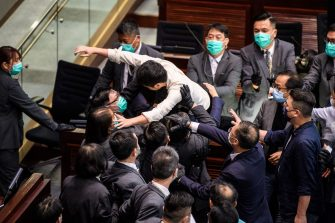 Pro-democracy lawmaker Ted Hui (C) is carried out by security during a scuffle with pro-Beijing lawmakers at the House Committee's election of chairpersons at the Legislative Council in Hong Kong on May 18, 2020. - Clashes broke out in Hong Kong's legislature for the second time this month on May 18 as the city's pro-democracy camp tried to scupper a controversial law that bans insulting China's national anthem. (Photo by Anthony WALLACE / AFP) (Photo by ANTHONY WALLACE/AFP via Getty Images)