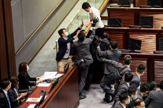 TOPSHOT - Pro-democracy lawmaker Ted Hui (top C) is surrounded by security during a scuffle with pro-Beijing lawmakers at the House Committee's election of chairpersons, presided by pro-Beijing lawmaker Chan Kin Por (bottom L) at the Legislative Council in Hong Kong on May 18, 2020. - Clashes broke out in Hong Kong's legislature for the second time this month on May 18 as the city's pro-democracy camp tried to scupper a controversial law that bans insulting China's national anthem. (Photo by Anthony WALLACE / AFP) (Photo by ANTHONY WALLACE/AFP via Getty Images)