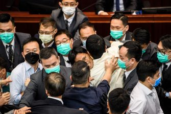 Pro-democracy lawmaker Eddie Chu (C) is surrounded by security during a scuffle with pro-Beijing lawmakers at the House Committee's election of chairpersons at the Legislative Council in Hong Kong on May 18, 2020. - Clashes broke out in Hong Kong's legislature for the second time this month on May 18 as the city's pro-democracy camp tried to scupper a controversial law that bans insulting China's national anthem. (Photo by Anthony WALLACE / AFP) (Photo by ANTHONY WALLACE/AFP via Getty Images)