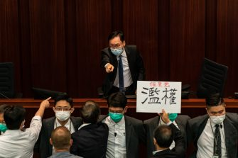 HONG KONG, CHINA - MAY 18: Pro Beijing lawmakers makes a gesture during a scuffle at the House Committee's election of chairpersons at the Legislative Council on May 18, 2020 in Hong Kong, China. Pro-democracy legislators were dragged out of the chamber by security guards as the two camps fought to control the House Committee which has been at a standstill for months.(Photo by Anthony Kwan/Getty Images)