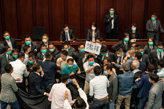 HONG KONG, CHINA - MAY 18: Pro democracy and pro Beijing lawmakers scuffle at the House Committee's election of chairpersons, presided by pro-Beijing lawmaker Chan Kin Por at the Legislative Council on May 18, 2020 in Hong Kong, China. Pro-democracy legislators were dragged out of the chamber by security guards as the two camps fought to control the House Committee which has been at a standstill for months.(Photo by Anthony Kwan/Getty Images)