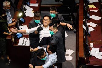 Pan-democratic politician, Lam Cheuk-ting (C) is removed by security after throwing papers torn from the Legco rulebook during a scuffle between pro-democracy and pro-Beijing lawmakers at the House Committee's election of chairpersons, at the Legislative Council in Hong Kong on May 18, 2020. - Clashes broke out in Hong Kong's legislature for the second time this month on May 18 as the city's pro-democracy camp tried to scupper a controversial law that bans insulting China's national anthem. (Photo by Anthony WALLACE / AFP) (Photo by ANTHONY WALLACE/AFP via Getty Images)