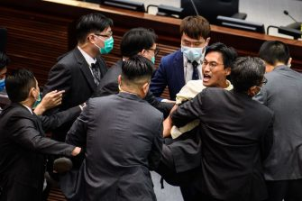Pro-democracy lawmaker Eddie Chu (C) is carried out by security during a scuffle with pro-Beijing lawmakers at the House Committee's election of chairpersons at the Legislative Council in Hong Kong on May 18, 2020. - Clashes broke out in Hong Kong's legislature for the second time this month on May 18 as the city's pro-democracy camp tried to scupper a controversial law that bans insulting China's national anthem. (Photo by Anthony WALLACE / AFP) (Photo by ANTHONY WALLACE/AFP via Getty Images)