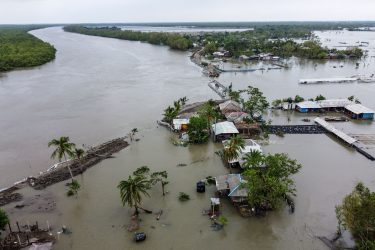 An aerial view shows flooded houses and buildings as a dam broke after the landfall of cyclone Amphan in Shyamnagar on May 21, 2020. - At least 22 people died as the fiercest cyclone to hit parts of Bangladesh and eastern India this century sent trees flying and flattened houses, with millions crammed into shelters despite the risk of coronavirus. (Photo by Munir uz Zaman / AFP) (Photo by MUNIR UZ ZAMAN/AFP via Getty Images)