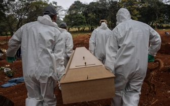 Employees carry the coffin of a person who died from COVID-19 at the Vila Formosa cemetery, in the outskirts of Sao Paulo, Brazil on May 20, 2020. - Brazil has emerged as the latest flashpoint in the coronavirus pandemic. The country has registered more than 270,000 cases and nearly 18,000 deaths so far, and the increase in infections is not expected to peak until June. (Photo by NELSON ALMEIDA / AFP) (Photo by NELSON ALMEIDA/AFP via Getty Images)