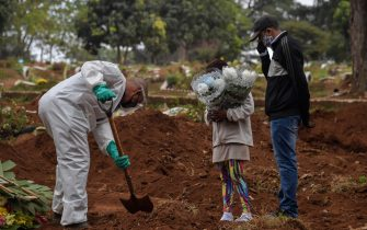 An employee digs next to relatives of a person who died from COVID-19 at the Vila Formosa cemetery, in the outskirts of Sao Paulo, Brazil on May 20, 2020. - Brazil has emerged as the latest flashpoint in the coronavirus pandemic. The country has registered more than 270,000 cases and nearly 18,000 deaths so far, and the increase in infections is not expected to peak until June. (Photo by NELSON ALMEIDA / AFP) (Photo by NELSON ALMEIDA/AFP via Getty Images)