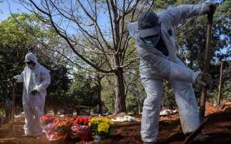 Employees bury a person who died from COVID-19 at the Vila Formosa cemetery, in the outskirts of Sao Paulo, Brazil on May 20, 2020. - Brazil has emerged as the latest flashpoint in the coronavirus pandemic. The country has registered more than 270,000 cases and nearly 18,000 deaths so far, and the increase in infections is not expected to peak until June. (Photo by NELSON ALMEIDA / AFP) (Photo by NELSON ALMEIDA/AFP via Getty Images)