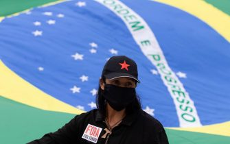 epa08434289 A woman participates in a protest against the President of Brazil, Jair Bolsonaro, at the Planalto Palace in Brasilia, Brazil, 20 May 2020. Convened by the members of the popular committee 'Bolsonaro Out', dozens of people participated in the demonstration that rejected Bolsonaro's statements and actions during the handling of the coronavirus crisis, which left more than 17,000 deaths in the South American country.  EPA/JOEDSON ALVES