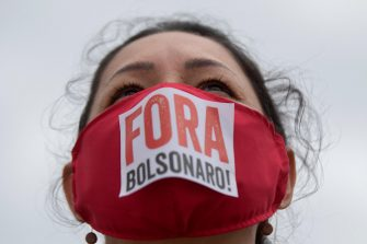 epa08434294 A woman participates in a protest against the President of Brazil, Jair Bolsonaro, at the Planalto Palace in Brasilia, Brazil, 20 May 2020. Convened by the members of the popular committee 'Bolsonaro Out', dozens of people participated in the demonstration that rejected Bolsonaro's statements and actions during the handling of the coronavirus crisis, which left more than 17,000 deaths in the South American country.  EPA/JOEDSON ALVES