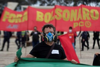 epa08434291 A man with a gas mask participates in a protest against the President of Brazil, Jair Bolsonaro, at the Planalto Palace in Brasilia, Brazil, 20 May 2020. Convened by the members of the popular committee 'Bolsonaro Out', dozens of people participated in the demonstration that rejected Bolsonaro's statements and actions during the handling of the coronavirus crisis, which left more than 17,000 deaths in the South American country.  EPA/JOEDSON ALVES