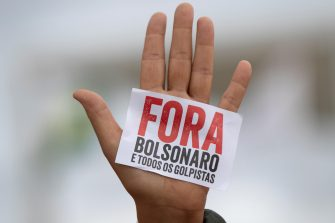 epa08434288 Detail of a hand that shows a small sign that reads 'Out Bolsonaro and all the coup leaders', during a protest against the President of Brazil, Jair Bolsonaro, at the Planalto Palace in Brasilia, Brazil, 20 May 2020. Convened by the members of the popular committee 'Bolsonaro Out', dozens of people participated in the demonstration that rejected Bolsonaro's statements and actions during the handling of the coronavirus crisis, which left more than 17,000 deaths in the South American country.  EPA/JOEDSON ALVES