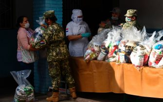 Soldiers distribute kits with supplies to residents at a low-income area in Asuncion on May 20, 2020, amid the new coronavirus pandemic. - More than 25,000 Paraguayan citizens prepare to return to their homeland fleeing the coronavirus pandemic, which efects have made them lose their jobs in Argentina, Brazil, Spain and the United States. (Photo by NORBERTO DUARTE / AFP) (Photo by NORBERTO DUARTE/AFP via Getty Images)