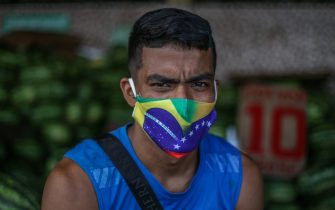 MANAUS, BRAZIL - MAY 20: Portrait of a man wearing a protective mask with both brazilian and venezuelan flags at Manaus Moderna market, on May 20 2020 in Manaus, Brazil. This traditional trade area in the Amazonas region remains in operation despite the coronavirus (COVID-19) pandemic.. (Photo by Andre Coelho/Getty Images)