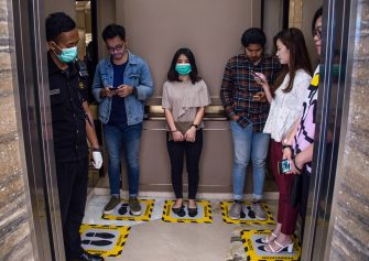 TOPSHOT - People stand on designated areas to ensure social distancing inside an elevator at a shopping mall in Surabaya on March 19, 2020, amid concerns of the COVID-19 coronavirus outbreak. (Photo by JUNI KRISWANTO / AFP) (Photo by JUNI KRISWANTO/AFP via Getty Images)