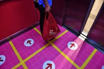 TOPSHOT - A shopper stands in an elevator marked for people to maintain social distancing, in an effort to contain the COVID-19 coronavirus, at Central Pinklao shopping mall in Bangkok on March 26, 2020. (Photo by Lillian SUWANRUMPHA / AFP) (Photo by LILLIAN SUWANRUMPHA/AFP via Getty Images)