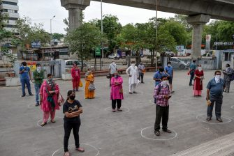 TOPSHOT - Customers stand on circles marked on the ground to maintain social distanciation as they wait to enter the Reliance Mart mall during a government-imposed nationwide lockdown as a preventive measure against the COVID-19 coronavirus in Ahmedabad on March 26, 2020. (Photo by SAM PANTHAKY / AFP) (Photo by SAM PANTHAKY/AFP via Getty Images)