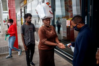 A mall clerk sanitises a customer's hands at the entrance of a shopping mall in Alexandra, Johannesburg, on April 10, 2020. - Alexandra township local workshop Hluvuku Designs transitioned its production from traditional textiles to reusable face masks to be distributed to its residents at the local mall to help curb the spread of the COVID-19 coronavirus. (Photo by Michele Spatari / AFP) (Photo by MICHELE SPATARI/AFP via Getty Images)