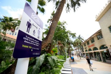 """MIAMI BEACH, FLORIDA - MAY 20:   Signage reminds people to  social distance on Lincoln Mall, May 20, 2020 in Miami Beach, Florida. The city of Miami Beach is allowing non-essential """"retail stores, personal grooming establishments, offices and museums"""" to reopen staring today.  (Photo by Cliff Hawkins/Getty Images)"""