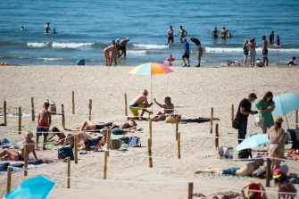 People sunbath at 'Couchant or Sunset beach' in roped off distancing zones marked out by the municipality along the beach in La Grande Motte, southern France, on May 21, 2020, as the nation eases lockdown measures taken to curb the spread of the COVID-19 pandemic, caused by the novel coronavirus. - The local municipality dubbed this set up 'organized beaches', the first in France to implement separated zones for beach goers in order to respect social distancing. (Photo by CLEMENT MAHOUDEAU / AFP)