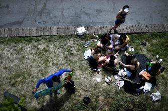 A group of friends sits on the grass and enjoy the sun on the banks of the river Seine, in Paris, on May 21, 2020 as France eases lockdown measures taken to curb the spread of the COVID-19 (the novel coronavirus). (Photo by STEPHANE DE SAKUTIN / AFP)