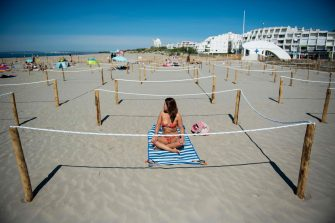 TOPSHOT - A woman sunbathes at 'Couchant or Sunset beach' in a roped off distancing zone marked out by the municipality along the beaches in La Grande Motte, southern France, on May 21, 2020, as the nation eases lockdown measures taken to curb the spread of the COVID-19 pandemic, caused by the novel coronavirus. - The local municipality dubbed this set up 'organized beaches', the first in France to implement separated zones for beach goers in order to respect social distancing. (Photo by CLEMENT MAHOUDEAU / AFP)