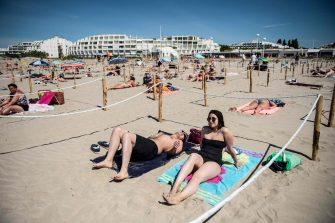 Two people sunbath at 'Couchant or Sunset beach', in a roped off distancing zone marked out by the municipality along the beach in La Grande Motte, southern France, on May 21, 2020, as the nation eases lockdown measures taken to curb the spread of the COVID-19 pandemic, caused by the novel coronavirus. - The local municipality dubbed this set up 'organized beaches', the first in France to implement separated zones for beach goers in order to respect social distancing. (Photo by CLEMENT MAHOUDEAU / AFP)
