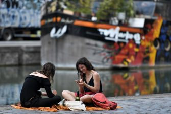 Two women laugh and speak as they have a pic-nic on the banks of the canal, in Paris, on May 21, 2020 as France eases lockdown measures taken to curb the spread of the COVID-19 (the novel coronavirus). (Photo by STEPHANE DE SAKUTIN / AFP)