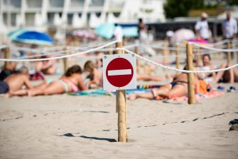 A no entry sign is attached to a wooden pilar at 'Couchant or Sunset beach', as sunbathers sit or lie in roped off distancing zones marked out by the municipality along the beach in La Grande Motte, southern France, on May 21, 2020, as the nation eases lockdown measures taken to curb the spread of the COVID-19 pandemic, caused by the novel coronavirus. - The local municipality dubbed this set up 'organized beaches', the first in France to implement separated zones for beach goers in order to respect social distancing. (Photo by CLEMENT MAHOUDEAU / AFP)