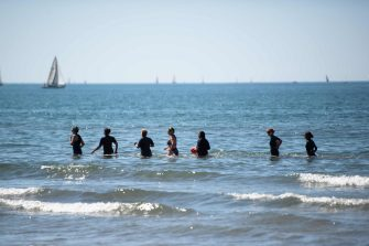 People jog in the sea at 'Couchant or Sunset beach' in La Grande Motte, southern France, on May 21, 2020, as the nation eases lockdown measures taken to curb the spread of the COVID-19 pandemic, caused by the novel coronavirus. - The local municipality dubbed this set up 'organized beaches', the first in France to implement separated zones for beach goers in order to respect social distancing. (Photo by CLEMENT MAHOUDEAU / AFP)