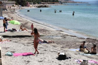 People take a sun bath and a swim at the Ricanto beach in Ajaccio on May 21, 2020 as the nearly all the beaches of the island reopen today on the French Mediterranean island of Corsica. (Photo by Pascal POCHARD-CASABIANCA / AFP)
