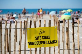 "A placard reading ""Site under video surveillance"" is attached to a wooden fence a people sunbathes at 'Couchant or Sunset beach' in roped off distancing zones marked out by the municipality along the beach in La Grande Motte, southern France, on May 21, 2020, as the nation eases lockdown measures taken to curb the spread of the COVID-19 pandemic, caused by the novel coronavirus. - The local municipality dubbed this set up 'organized beaches', the first in France to implement separated zones for beach goers in order to respect social distancing. (Photo by CLEMENT MAHOUDEAU / AFP)"