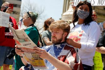 "A person reads a newspaper as he gets his hair cut during the Michigan Conservative Coalition organized ""Operation Haircut"" outside the Michigan State Capitol in Lansing, Michigan on May 20, 2020. - The group is protesting Michigan Governor Gretchen Whitmer's mandatory closure to curtail the coronavirus pandemic. (Photo by JEFF KOWALSKY / AFP) (Photo by JEFF KOWALSKY/AFP via Getty Images)"