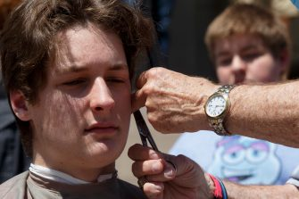 LANSING, MI - MAY 20: Owosso barber, Karl Manke, gives a free haircut to Parker Shonts, of Lake Orion, on the steps of the state Capitol during Operation Haircut on May 20, 2020 in Lansing, Michigan. The event was a protest planned by the Michigan Conservative Coalition in response to an Owosso barber, Karl Manke, whose business license was taken away after he violated the stay-at-home order by reopening. The protest is part of a growing national movement against stay-at-home orders that are designed to help slow the spread of the coronavirus (COVID-19). (Photo by Elaine Cromie/Getty Images)