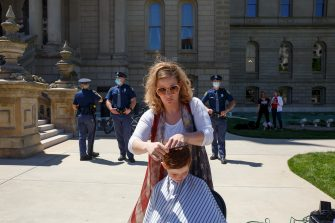 LANSING, MI - MAY 20: Danielle Ashcraft gives a free haircut to a child near the steps of the state Capitol during Operation Haircut on May 20, 2020 in Lansing, Michigan. The event was a protest planned by the Michigan Conservative Coalition in response to an Owosso barber, Karl Manke, whose business license was taken away after he violated the stay-at-home order by reopening. The protest is part of a growing national movement against stay-at-home orders that are designed to help slow the spread of the coronavirus (COVID-19). (Photo by Elaine Cromie/Getty Images)