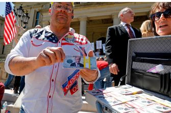 "A man holds up fake USA Dollars with Donald Trumps photo on the face during the Michigan Conservative Coalition organized ""Operation Haircut"" outside the Michigan State Capitol in Lansing, Michigan on May 20, 2020. - The group is protesting Michigan Governor Gretchen Whitmer's mandatory closure to curtail the coronavirus pandemic. (Photo by JEFF KOWALSKY / AFP) (Photo by JEFF KOWALSKY/AFP via Getty Images)"
