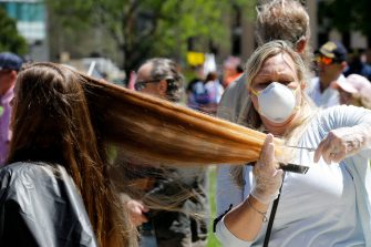 "TOPSHOT - Randi Bates cuts hair during the Michigan Conservative Coalition organized ""Operation Haircut"" outside the Michigan State Capitol in Lansing, Michigan on May 20, 2020. - The group is protesting Michigan Governor Gretchen Whitmer's mandatory closure to curtail the coronavirus pandemic. (Photo by JEFF KOWALSKY / AFP) (Photo by JEFF KOWALSKY/AFP via Getty Images)"