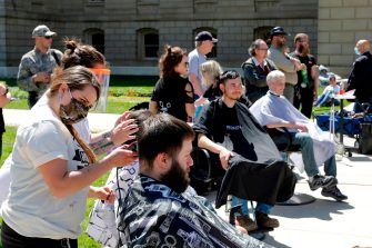 "Barbers cut hair during the Michigan Conservative Coalition organized ""Operation Haircut"" outside the Michigan State Capitol in Lansing, Michigan on May 20, 2020. - The group is protesting Michigan Governor Gretchen Whitmer's mandatory closure to curtail the coronavirus pandemic. (Photo by JEFF KOWALSKY / AFP) (Photo by JEFF KOWALSKY/AFP via Getty Images)"
