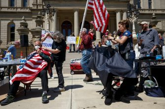 LANSING, MI - MAY 20: Annette Refacz, left, and Angela Rigas give free haircuts near the steps of the state Capitol during Operation Haircut on May 20, 2020 in Lansing, Michigan. The event was a protest planned by the Michigan Conservative Coalition in response to an Owosso barber, Karl Manke, whose business license was taken away after he violated the stay-at-home order by reopening. The protest is part of a growing national movement against stay-at-home orders that are designed to help slow the spread of the coronavirus (COVID-19). (Photo by Elaine Cromie/Getty Images)