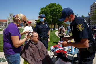 LANSING, MI - MAY 20: An officer gives a warning to Brenda, a barber who didnt give her last name, as she was giving a free haircut near the steps of the state Capitol during Operation Haircut on May 20, 2020 in Lansing, Michigan. The event was a protest planned by the Michigan Conservative Coalition in response to an Owosso barber, Karl Manke, whose business license was taken away after he violated the stay-at-home order by reopening. The protest is part of a growing national movement against stay-at-home orders that are designed to help slow the spread of the coronavirus (COVID-19). (Photo by Elaine Cromie/Getty Images)