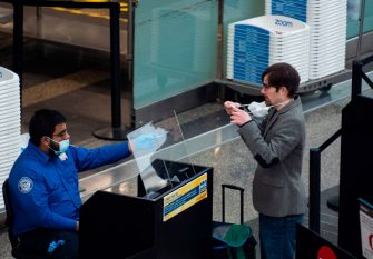 A passenger removes his mask as he has his ID checked by a Transportation Security Administration (TSA) employee in Ronald Reagan Washington National Airport in Arlington, Virginia, on May 12, 2020. - The airline industry has been hit hard by the COVID-19 pandemic, with the number of people flying having decreased by more than 90 percent since the beginning of March. (Photo by ANDREW CABALLERO-REYNOLDS / AFP) (Photo by ANDREW CABALLERO-REYNOLDS/AFP via Getty Images)