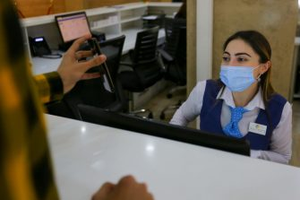 BAKU, AZERBAIJAN - MAY 20: A young woman wearing a protective facemask and check online document inside ASAN service in Baku on May 20, 2020 in Baku, Azerbaijan. The coronavirus outbreak has infected more than 4.9 million people across the world. Azerbaijan has reported 3518 cases of COVID-19 and 41 deaths.(Photo by Aziz Karimov/Getty Images)